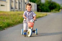 Bambini che guidano una bicicletta sulla via Fotografia Stock Libera da Diritti