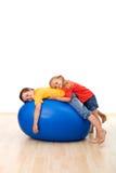 Bambini che hanno divertimento distendersi su una grande sfera di gomma Immagini Stock Libere da Diritti