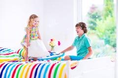Bambini che hanno lotta di cuscino Immagine Stock