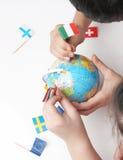 Bambini che indicano le bandierine sul globo del mondo Fotografia Stock
