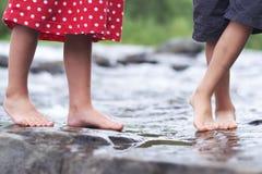 Bambini che inzuppano i piedi in un ruscello immagine stock