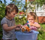 Bambini che lavano i piatti all'aperto Fotografie Stock Libere da Diritti