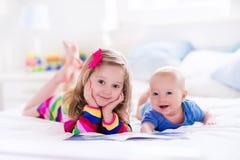 Bambini che leggono nella camera da letto bianca Fotografia Stock