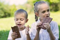 Bambini che mangiano cioccolato all'aperto immagini stock