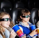 Bambini che mangiano gli spuntini nel teatro del cinema 3D Immagine Stock Libera da Diritti