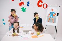 Bambini che mangiano le mele mentre sedendosi nell'aula durante la pausa Immagine Stock Libera da Diritti