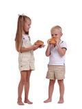 Bambini che mangiano pasticceria isolata su un fondo bianco Fratello sveglio e sorella che mangiano i panini di cannella Concetto Fotografie Stock Libere da Diritti