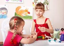 Bambini che modellano plasticine in playroom. Fotografia Stock Libera da Diritti