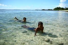 Bambini che nuotano nella spiaggia della Samoa fotografie stock libere da diritti