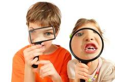 Bambini che osservano tramite le lenti d'ingrandimento Fotografia Stock