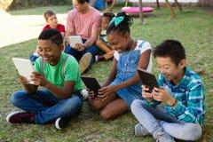 Bambini che per mezzo del computer della compressa con l'uomo al parco Fotografia Stock Libera da Diritti