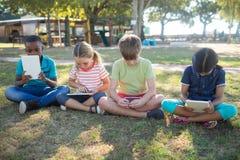Bambini che per mezzo del computer della compressa mentre sedendosi sul campo erboso Immagine Stock