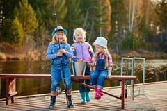 Bambini che pescano con le canne da pesca Giorno caldo di autunno Pescando su un pontone di legno fotografie stock libere da diritti