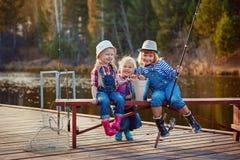 Bambini che pescano con le canne da pesca Giorno caldo di autunno Pescando su un pontone di legno fotografia stock