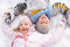 Bambini che pongono sull'angelo di fabbricazione al suolo della neve Fotografia Stock