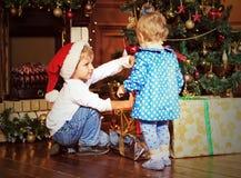 Bambini che prendono i presente nell'interno di natale Fotografia Stock