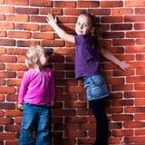 Bambini che propongono contro la parete della rottura Immagini Stock Libere da Diritti