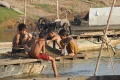 Bambini che raccolgono i mitili del fiume Fotografia Stock
