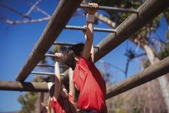 Bambini che scalano le barre di scimmia durante l'addestramento di corsa ad ostacoli fotografia stock