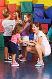 Bambini che si esercitano con l'insegnante della scuola materna in palestra Immagine Stock