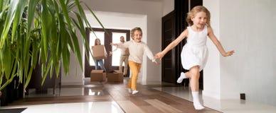 Bambini che si imbattono nei genitori della nuova casa con le scatole su fondo immagine stock libera da diritti