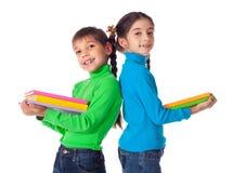 Bambini che si levano in piedi con la pila di libri Fotografia Stock