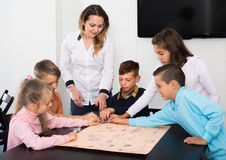 Bambini che si siedono alla tavola con il gioco da tavolo ed ai dadi alla scuola Immagine Stock Libera da Diritti