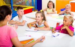 Bambini che si siedono ed insegnante d'ascolto in scuola elementare Immagine Stock Libera da Diritti