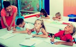 Bambini che si siedono ed insegnante d'ascolto in scuola elementare Fotografia Stock