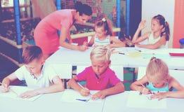 Bambini che si siedono ed insegnante d'ascolto in scuola elementare Fotografie Stock Libere da Diritti