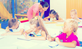 Bambini che si siedono ed insegnante d'ascolto in scuola elementare Immagini Stock