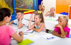 Bambini che si siedono ed insegnante d'ascolto in scuola elementare Immagini Stock Libere da Diritti