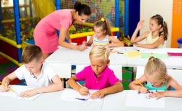 Bambini che si siedono ed insegnante d'ascolto in scuola elementare Immagine Stock