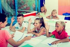 Bambini che si siedono ed insegnante d'ascolto in scuola elementare Fotografie Stock