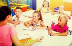 Bambini che si siedono ed insegnante d'ascolto in scuola elementare Fotografia Stock Libera da Diritti