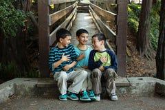 Bambini che si siedono insieme ridere scioccamente fotografia stock libera da diritti