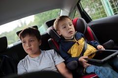 Bambini che si siedono nell'automobile e che esaminano Immagine Stock