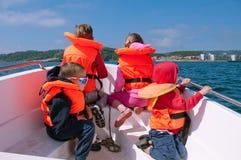 Bambini che si siedono sull'arco di un motoscafo in un open water Fotografia Stock Libera da Diritti