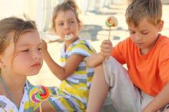 Bambini che si siedono sulla spiaggia e che mangiano i lollipops Fotografia Stock