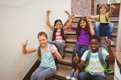 Bambini che si siedono sulle scale a scuola Immagine Stock