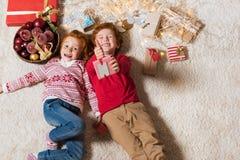 Bambini che si trovano sul pavimento con i regali Immagini Stock Libere da Diritti