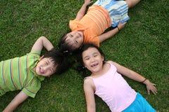 Bambini che si trovano sull'erba Fotografie Stock Libere da Diritti