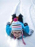 Bambini che Sledding giù la collina della neve su velocità veloce della slitta Immagine Stock