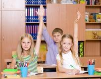 Bambini che sollevano le mani che conoscono la risposta alla domanda Fotografie Stock Libere da Diritti