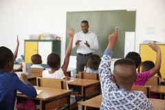 Bambini che sollevano le mani durante la lezione ad una scuola elementare Immagine Stock