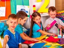 Bambini che tengono carta colorata sulla tavola dentro Immagine Stock Libera da Diritti