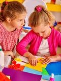 Bambini che tengono carta colorata sulla tavola dentro Fotografia Stock Libera da Diritti