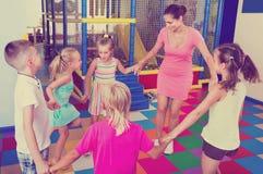 Bambini che tengono ogni altri mani e che ballano con l'insegnante Fotografia Stock Libera da Diritti