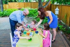 Bambini che tingono le uova di Pasqua con la madre ed il padre Immagini Stock Libere da Diritti