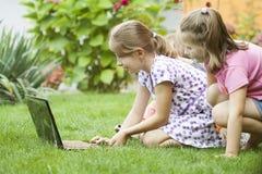 Bambini che utilizzano computer portatile nel prato Fotografie Stock